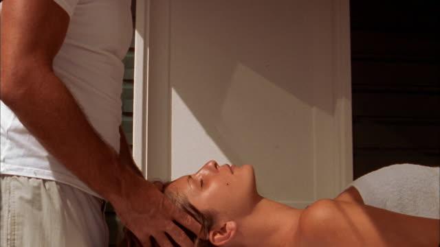 tilt down woman receiving head massage on massage table - head massage stock videos & royalty-free footage