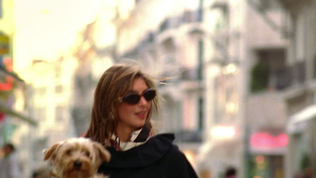 tilt down woman walking on street carrying small dog / paris, france - stereotypically upper class stock videos & royalty-free footage