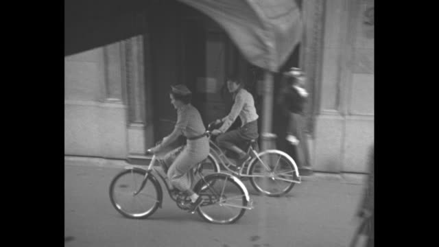 stockvideo's en b-roll-footage met tilt down women wearing hats ride bicycles on sidewalk past storefronts toward easter parade - 1930