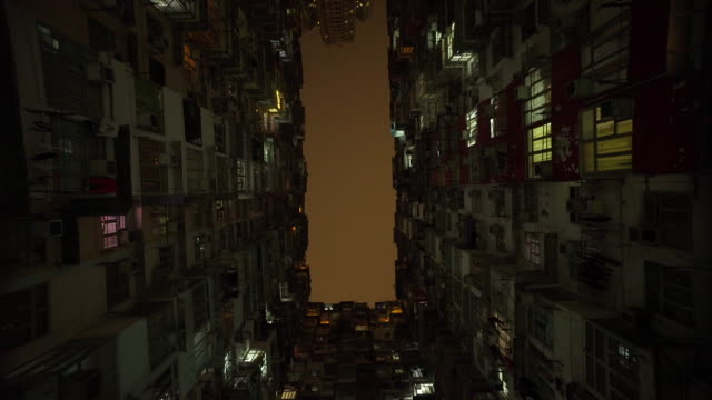 tilt down, worker in apartment complex in hong kong - inarcare la schiena video stock e b–roll