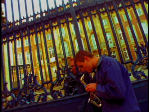 tilt down zoom in to close up young man playing toy saxophone by gate with man on other side / munich, germany - saxophone stock videos & royalty-free footage