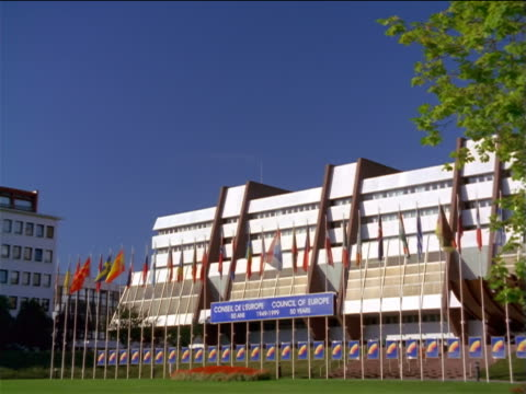 vidéos et rushes de tilt down pan zoom out council of europe building with flags, grass + flowers in foreground / strasbourg, france - gouvernement
