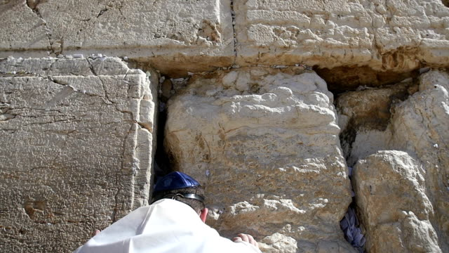 tilt down/man praying at the wailing wall, over the shoulder view, close-up/ jerusalem old city - wailing wall stock videos & royalty-free footage