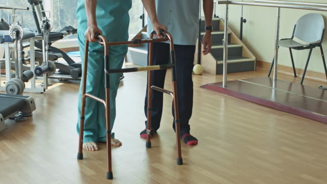 Tilt film video of physiotherapist helping senior man using walking frame