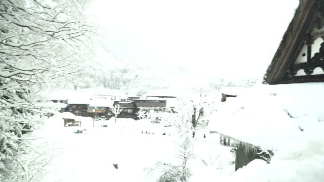 tilt from high level view: pediment of a japanese house at shirakawago village under snow - pediment stock videos & royalty-free footage