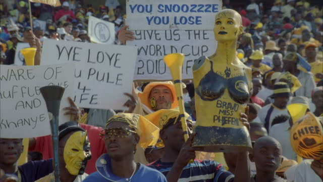 tilt of kaizer chiefs fans holding up signs and one of them holding up a mannequin - ハウテング州点の映像素材/bロール