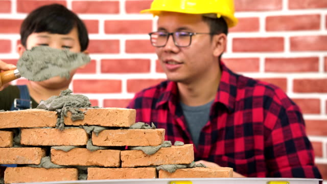 tilt on front view:son try to lay brick by himself with construction father's help on a new house - skill stock videos & royalty-free footage