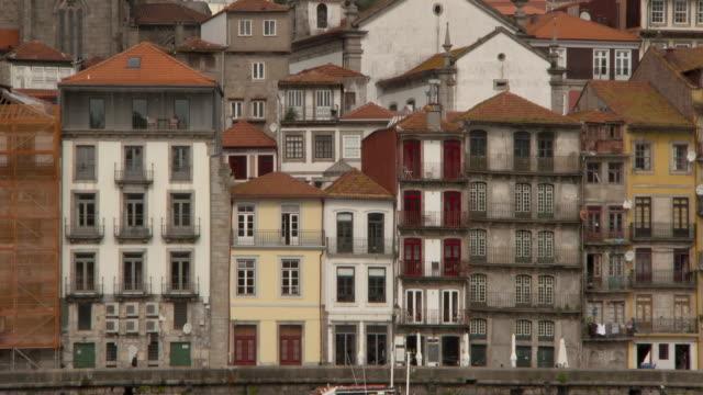 vídeos y material grabado en eventos de stock de tilt pan: porto catholic cathedral and riverfront architecture on cloudy day - detalle arquitectónico exterior