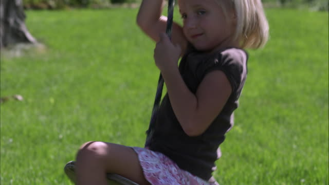 tilt shot of a little girl playing on a tree swing in slow motion - hair accessory stock videos & royalty-free footage