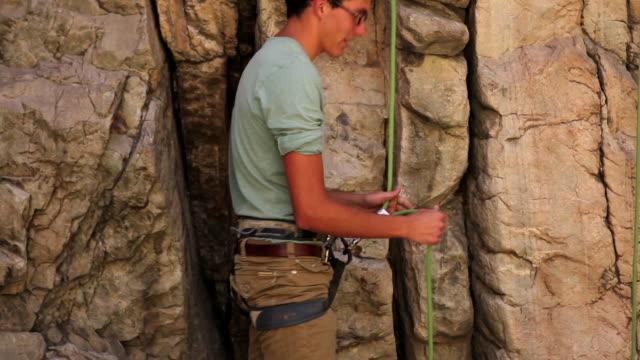 Tilt shot of a man adjusting a locking carabiner.