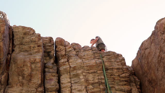 tilt shot of a rock-climber arranging a rope atop a cliff face. - rock face stock videos & royalty-free footage