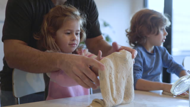 tilt shot of father assisting daughter in making dough while sitting with son at kitchen - genderblend stock-videos und b-roll-filmmaterial