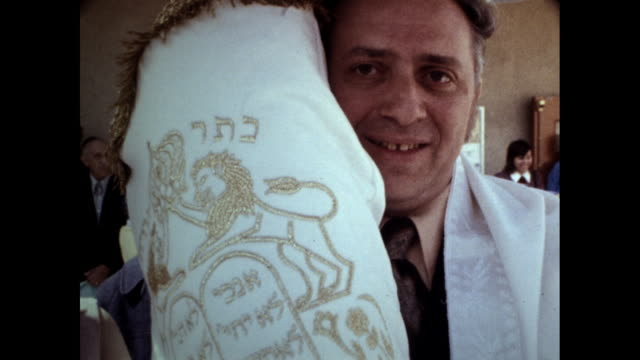 vídeos y material grabado en eventos de stock de tilt shot of man with gap teeth smiling at the camera holding a torah with embroidered cover with hebrew writing in gold - torah