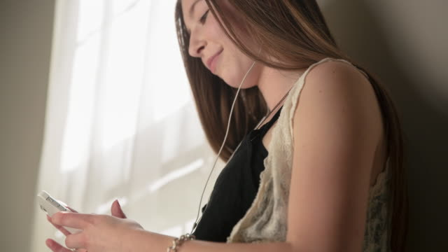 tilt shot of teenage girl listening music while using mobile phone by wall at home - one teenage girl only stock videos & royalty-free footage