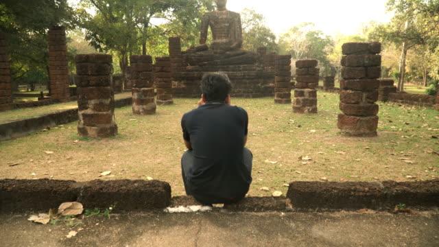 stockvideo's en b-roll-footage met tilt shot: jonge reiziger is het nemen van de foto van pachacamac, kamphaeng phet - menselijke rug