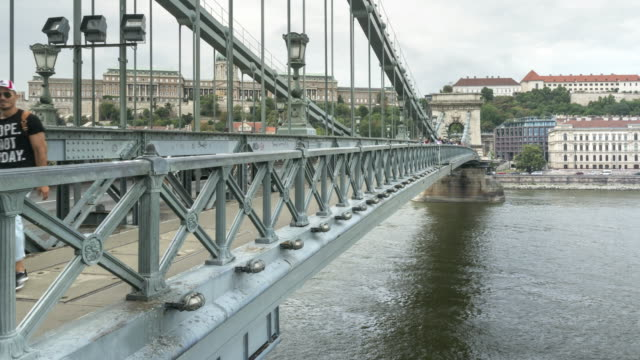 tilt tl: besucherauffahrt auf der szechenyi-kettenbrücke in budapest, ungarn am wochenende - chain bridge suspension bridge stock-videos und b-roll-filmmaterial