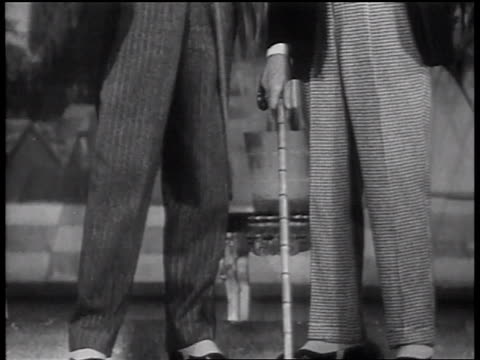 b/w 1937 tilt up 2 senior male models with canes modeling baggy pants, jackets, vests + hats - formal stock videos and b-roll footage