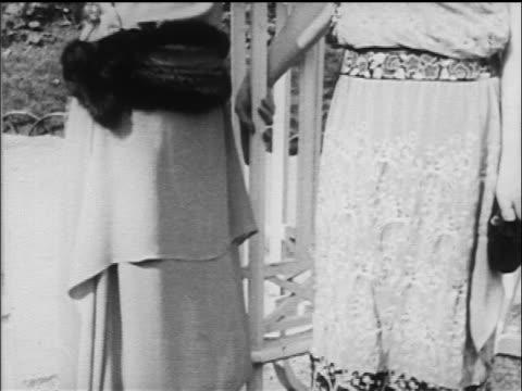 stockvideo's en b-roll-footage met b/w 1917 tilt up 2 women in dresses + hats talking outdoors / one in first cloche - 1917