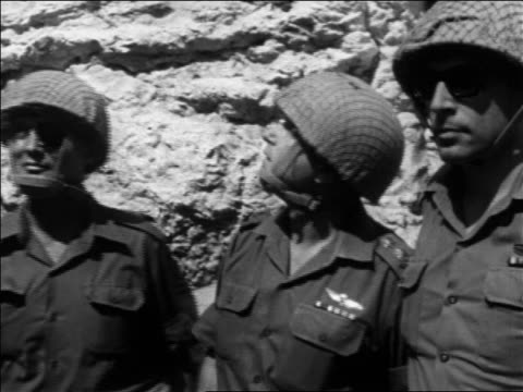 tilt up 3 soldiers looking up at wailing wall after six day war / jerusalem - 1967 bildbanksvideor och videomaterial från bakom kulisserna