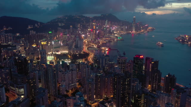 tilt up aerial of hong kong urban skyline in twilight time - victoria harbour hong kong stock videos & royalty-free footage