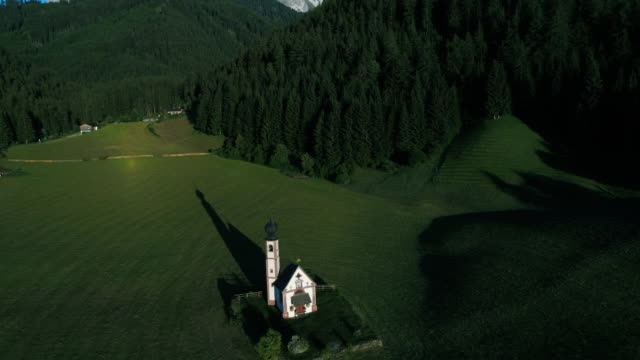 tilt up aerial shot showing an idyllic church with mountains in the background, dolomites, italy - 尖り屋根点の映像素材/bロール