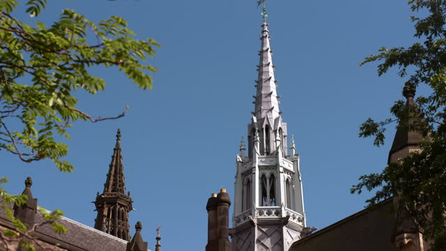 tilt up along the exterior of glasgow university building and spires on a bright sunny day with a clear blue skies in the background - antique stock videos & royalty-free footage