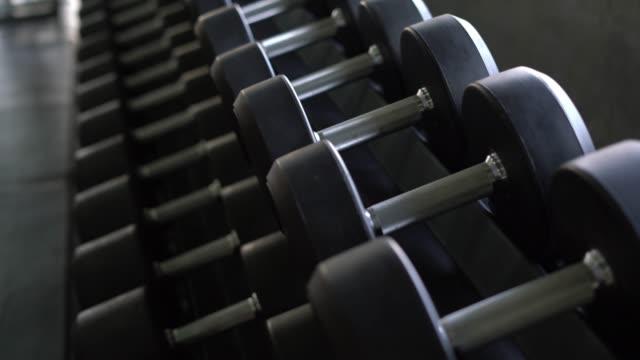 vídeos de stock, filmes e b-roll de levante e close-up de haltere no ginásio. - health club