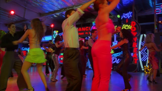 vídeos de stock, filmes e b-roll de tilt up and down as couple move across dance floor of neon lit night club, los angeles available in hd. - estilo dos anos 2000