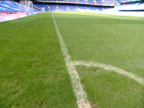Tilt up and pan left from corner flag markings to blue seats in football stand Stamford Bridge football stadium Chelsea