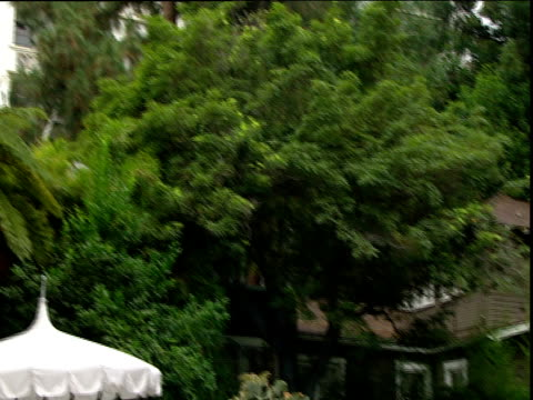 Tilt up and pan left from luxury cottage buried in lush greenery to Chateau Marmont hotel Sunset Strip Los Angeles