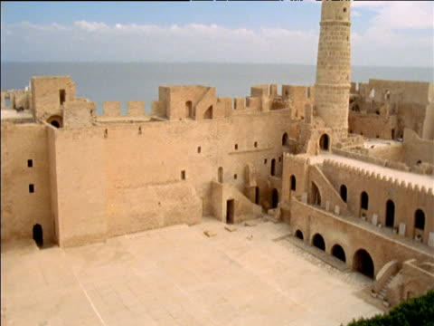 Tilt up and pan right from courtyard and walls of Arab fortress to tall round tower with red flag Monastir