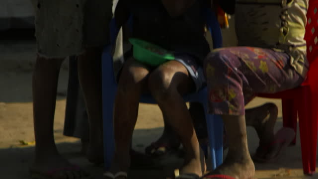 tilt up angolan handicapped girls hair braided by children - braided hair stock-videos und b-roll-filmmaterial
