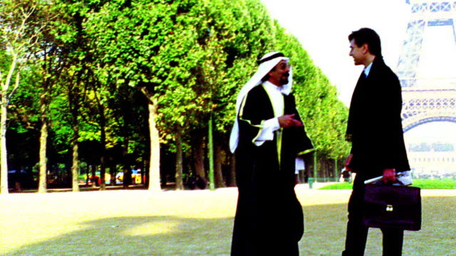 OVEREXPOSED tilt up PAN Arab man in headdress + robes talking to businessman by Eiffel Tower / Paris