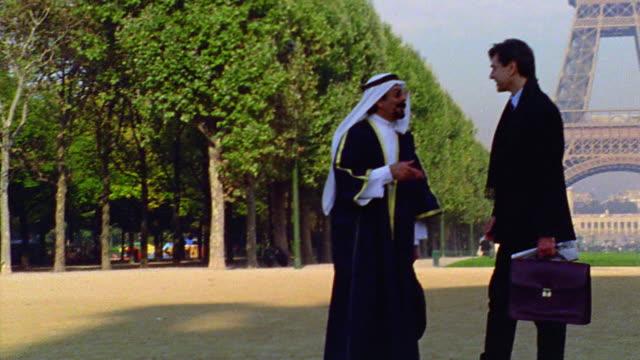 tilt up pan arab man in headdress + robes talking to businessman in front of eiffel tower / paris - headdress stock videos & royalty-free footage