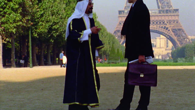 tilt up Arab man in robes + headdress talking to businessman with briefcase in front of Eiffel Tower /Paris