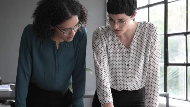 tilt up, architecture firm female employees look over blueprints - 18 19 years stock videos & royalty-free footage