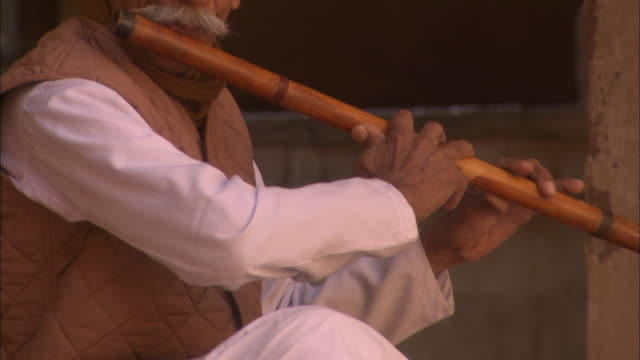Tilt up as elderly man taps feet whilst playing flute in courtyard of Mehrangarh Fort Jodhpur Rajasthan Available in HD.