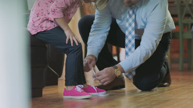 MS. Tilt up as father ties daughter's shoelaces and gives her high five in morning before work.