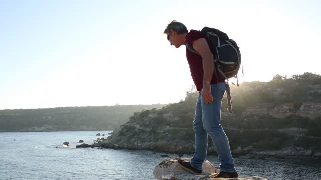 tilt up as male hiker arrives at rock promontory, looks off - 腰に手を当てる点の映像素材/bロール