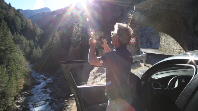 Tilt up as man steps out of car, takes digital tablet pic across mountain river