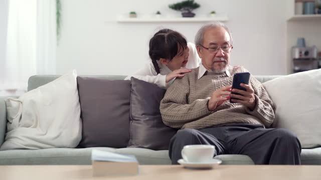 vídeos de stock e filmes b-roll de 4k uhd tilt up: asian girl playing peek-a-boo to her grandpa while he using his smart phone. - família de várias gerações