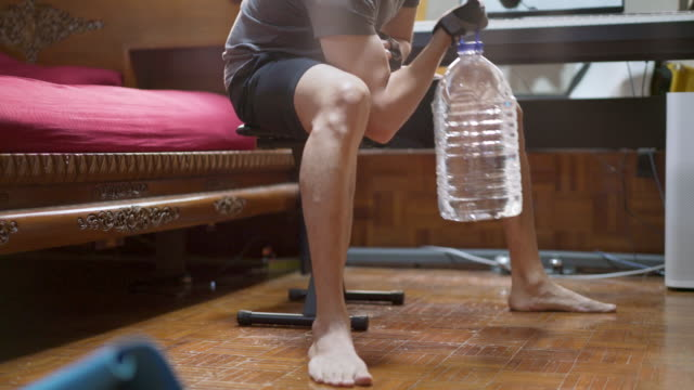 tilt up asian man using plastic gallon water bottle instead of gym weights for exercise at home in covid-19 or corona virus situation - sollevare video stock e b–roll