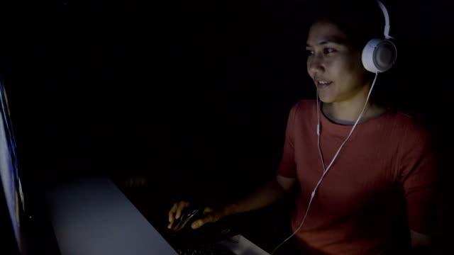 4 k ms は、アジアの女性が自宅の暗闇の中でコンピューター ゲームを傾けます。 - ゲーム点の映像素材/bロール