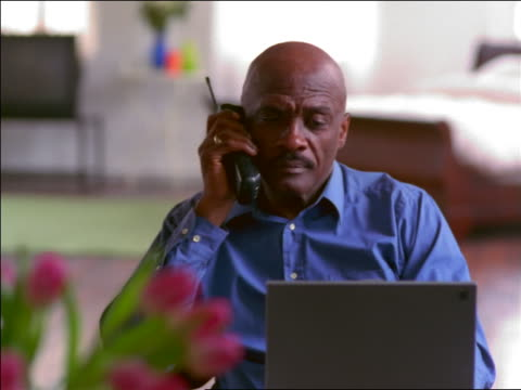 tilt up bald black man sitting in front of laptop computer talking on cordless phone - einzelner mann über 40 stock-videos und b-roll-filmmaterial