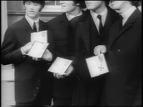 tilt up beatles holding medals outside of buckingham palace / london / newsreel - 1965 stock videos & royalty-free footage