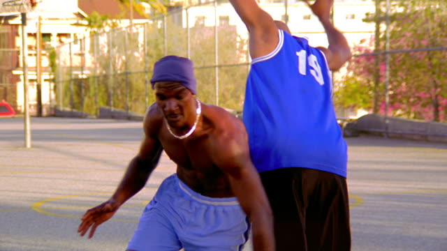 ms pan tilt up black man dribbling past other black man doing lay-up shot on outdoor basketball court - shooting baskets stock videos & royalty-free footage