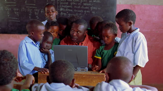 MS tilt up Black man sitting + using computer in classroom with children surrounding him / Kenya