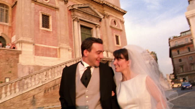 SHAKY tilt up bride + groom walking + kissing in front of Trinita dei Monti / Rome, Italy