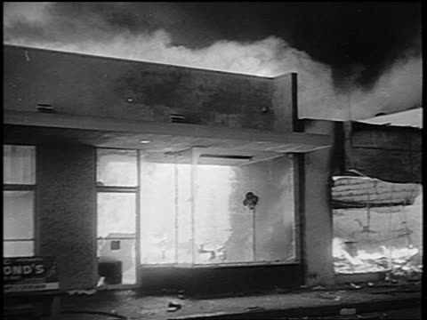 PAN tilt up building on fire during Watts race riots / Los Angeles / newsreel