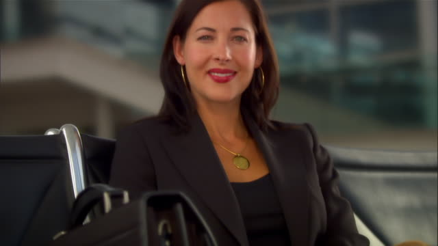 Tilt up businesswoman waiting for flight at airport smiling at camera